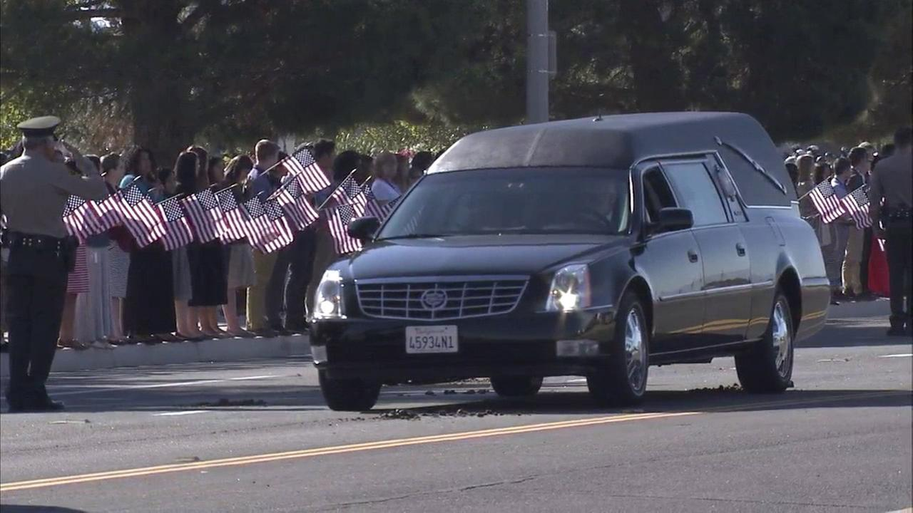 Bystanders hold American flags as a hearse drives past in a procession for L.A. County sheriffs Sgt. Steve Owen on Thursday, Oct. 13, 2016.KABC