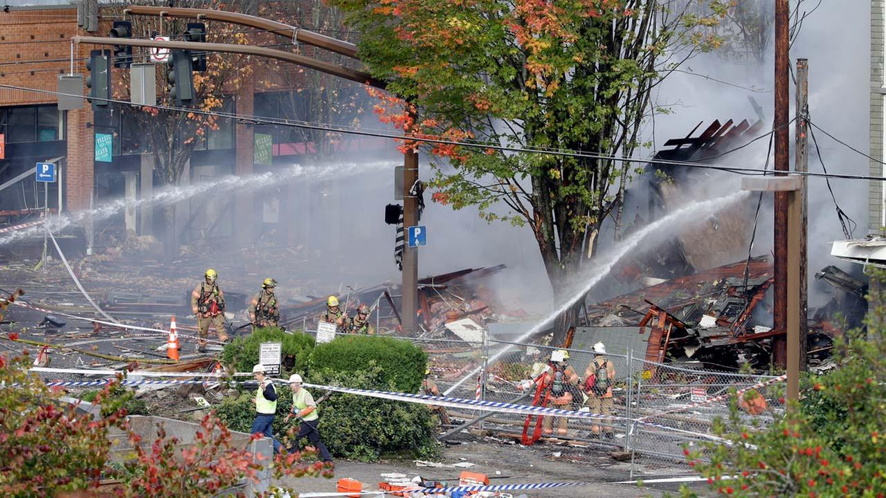 Firefighters battle a blaze after a gas explosion in Portland, Ore., Wednesday, Oct. 19, 2016. Two firefighters and two civilians were injured in the blast.