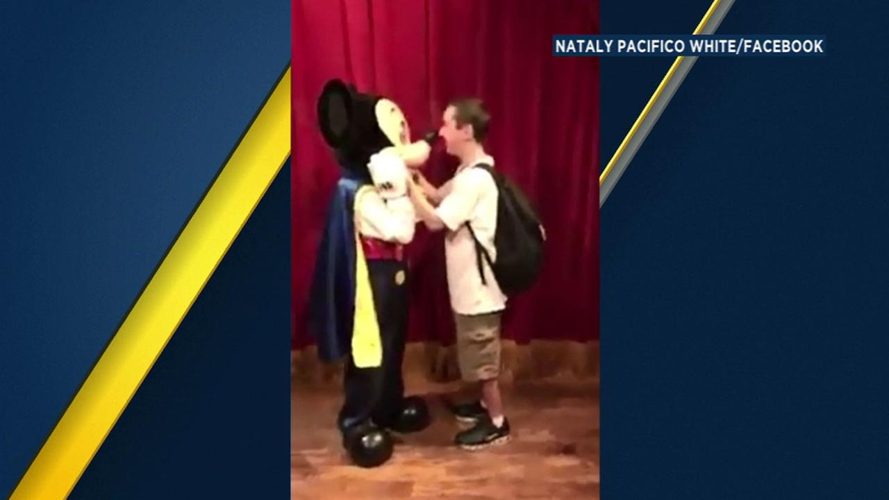 Basilio Santana touches noses with Mickey Mouse after they meet at Walt Disney World.
