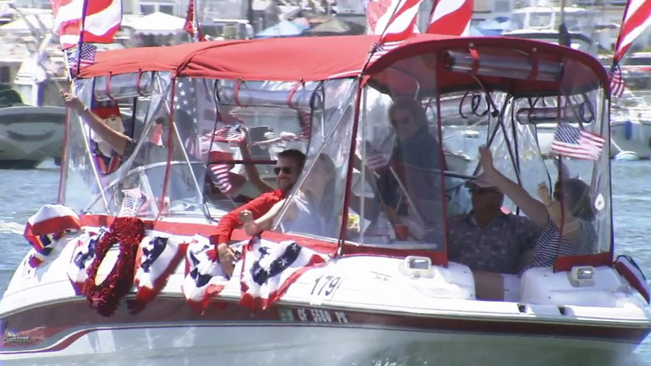 People wave to the crowds during the boat parade at Newport Beach on Friday, July 4, 2014.
