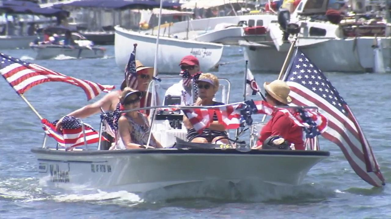 A boat wrapped with American flags participates in the boat parade at Newport Beach on Friday, July 4, 2014.