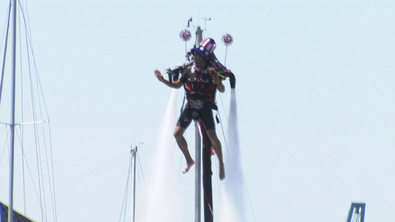 A man wearing a tall hat and dressed in patriotic colors rides a jet pack in Newport Beachs boat parade on Friday, July 4, 2014.