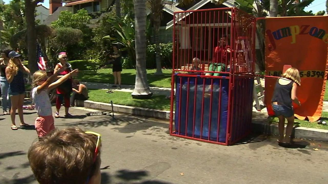 A girl pushes a button to dunk a boy into water at the Bluff Heights Neighborhood Associations block party in Long Beach on Friday, July 4, 2014.