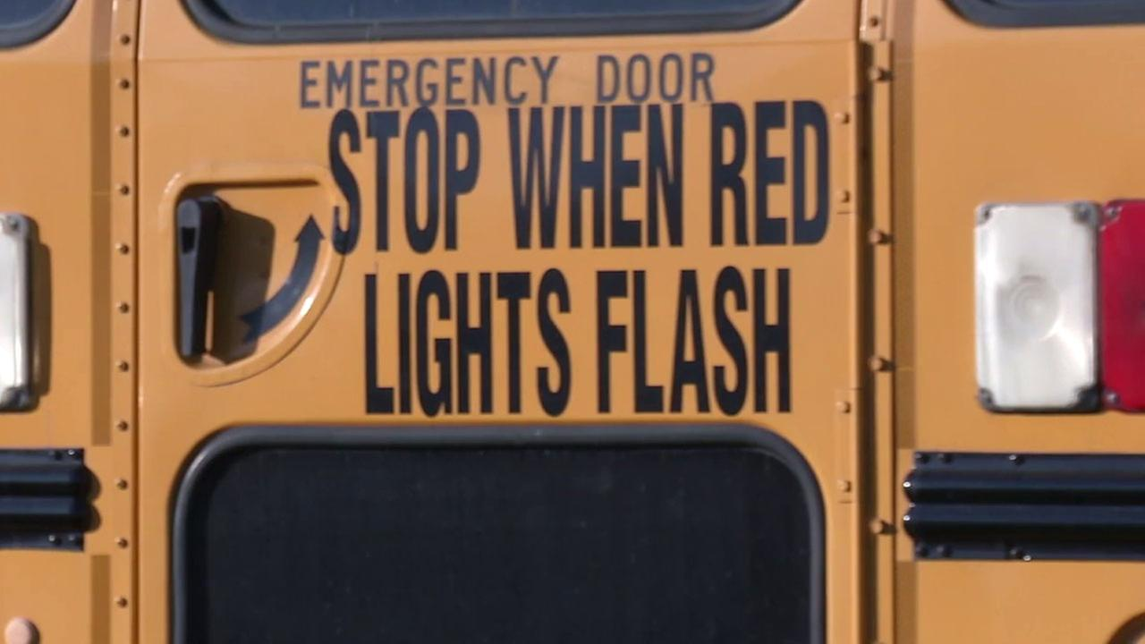 A photo shows the emergency door on the back of a school bus showing the warning stop when red lights flash.