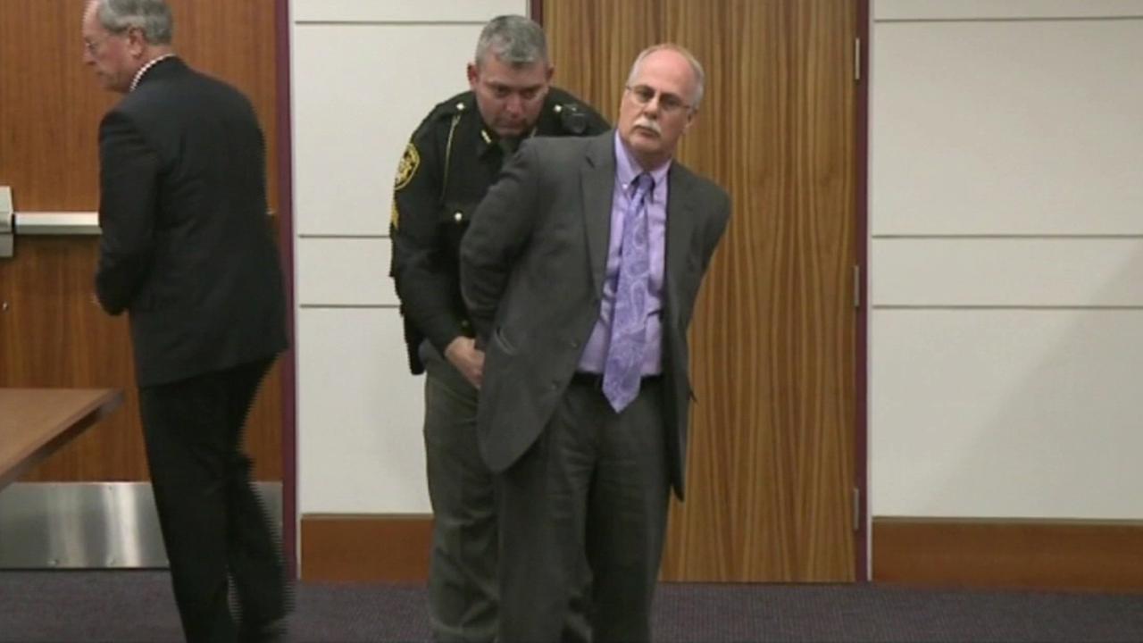 A bailiff handcuffs former Ohio attorney Michael Fine, 59, in a Lorain County courtroom.