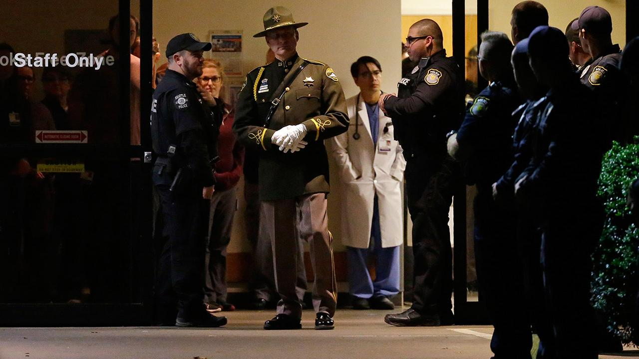Hospital and law enforcement workers stand at an entrance to Tacoma General Hospital in Tacoma, Wash., as they wait for the body of a Tacoma Police officer who was shot and killed.