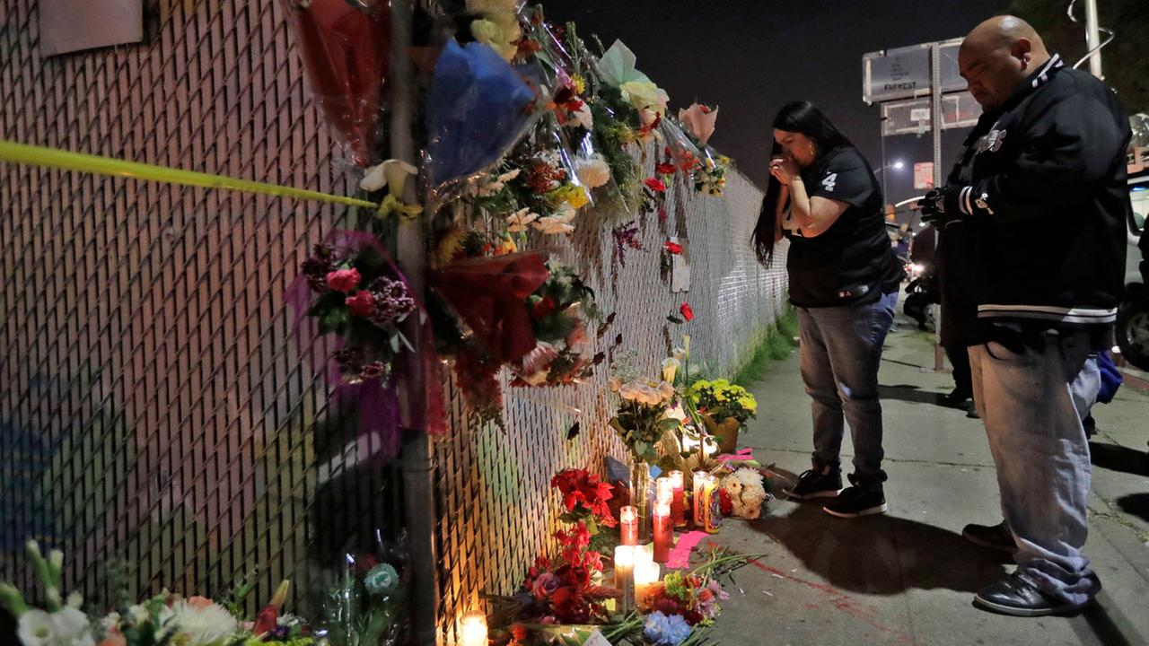 Sol Rodriguez, center, and Aaron Torres visit a shrine for the victims of a warehouse fire near the site Sunday, Dec. 4, 2016, in Oakland.