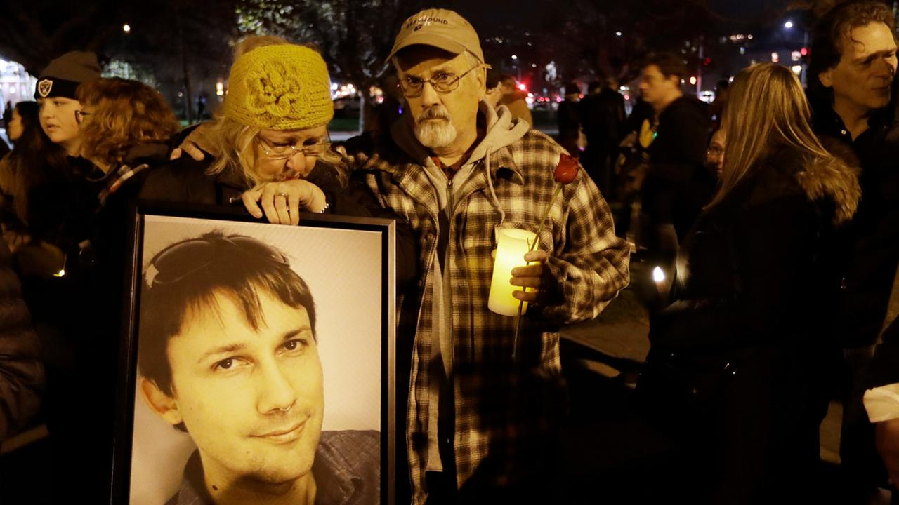 Judy Hough and her husband Brian hold a picture of their son Travis, who died in a warehouse fire, during a vigil at Lake Merritt on Monday, Dec. 5, 2016, in Oakland.