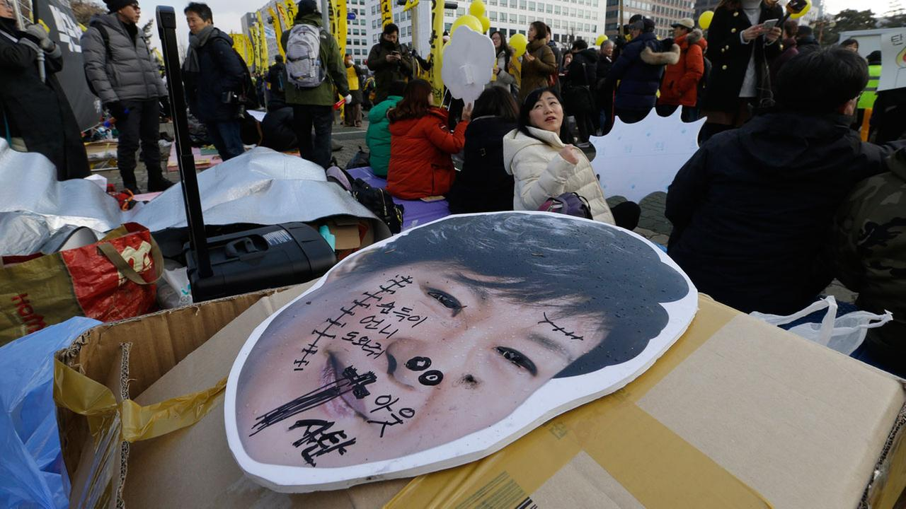 A defaced portrait of South Korean President Park Geun-hye is seen as protesters sit demanding the impeachment of Park in front of the National Assembly in South Korea.