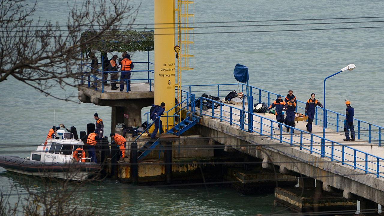 Russian rescue workers carry a body from the wreckage of the crashed plane, at a pier just outside Sochi, Russia, Sunday, Dec. 25, 2016.