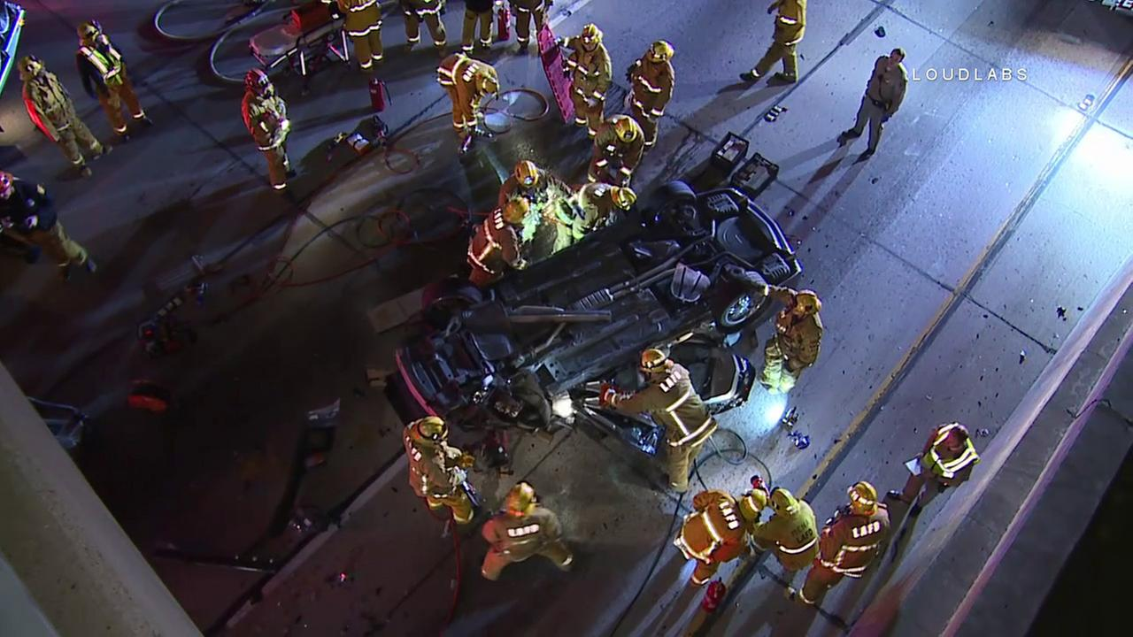 Los Angeles Fire Department and California Highway Patrol personnel are seen near an overturned vehicle after it landed on the 110 Freeway in downtown on Thursday, Dec. 29, 2016.
