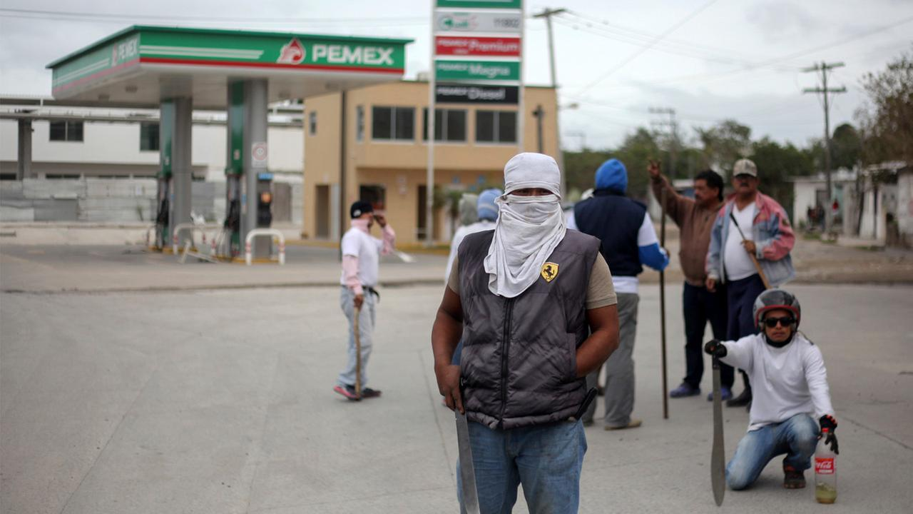 Masked men stand guard in front of a gas station in Veracruz, Mexico, Saturday, Jan. 7, 2017.