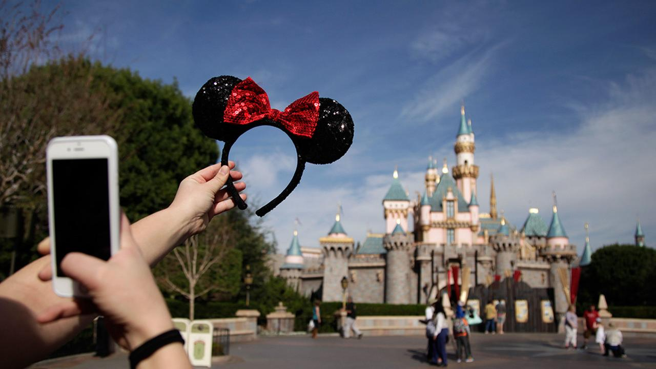 In this file photo, a guest takes pictures of her hairband with the Sleeping Beautys Castle in the background at Disneyland.