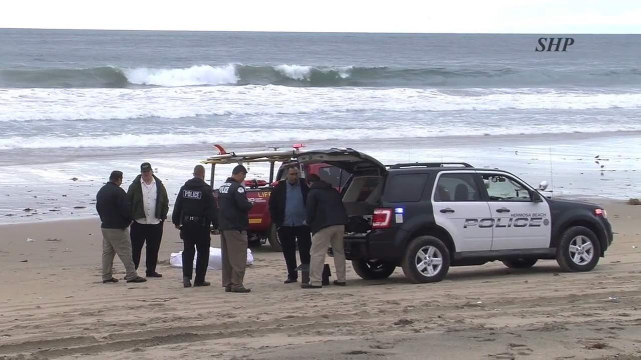 Law enforcement officials are seen in Hermosa Beach, where a womans body washed ashore on Friday, Jan. 13, 2107.