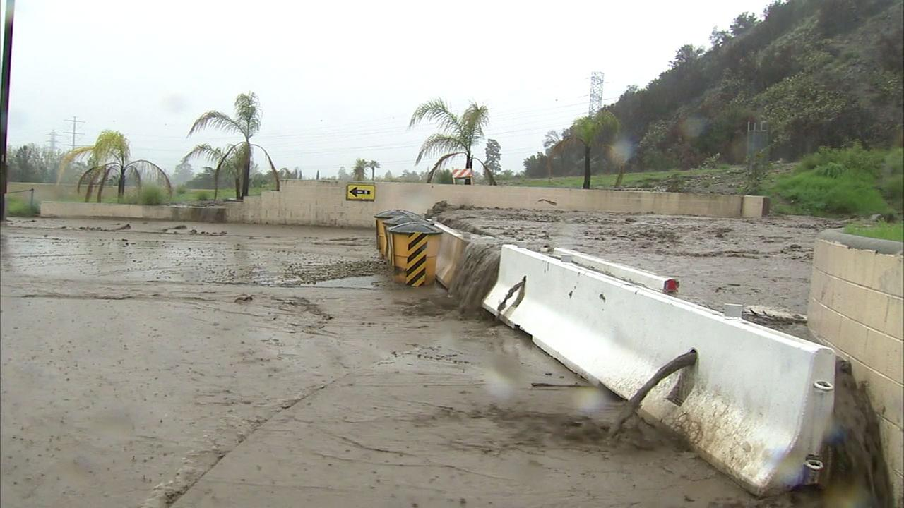 Heavy mud flowed around k-rails set up near Duarte hillsides.