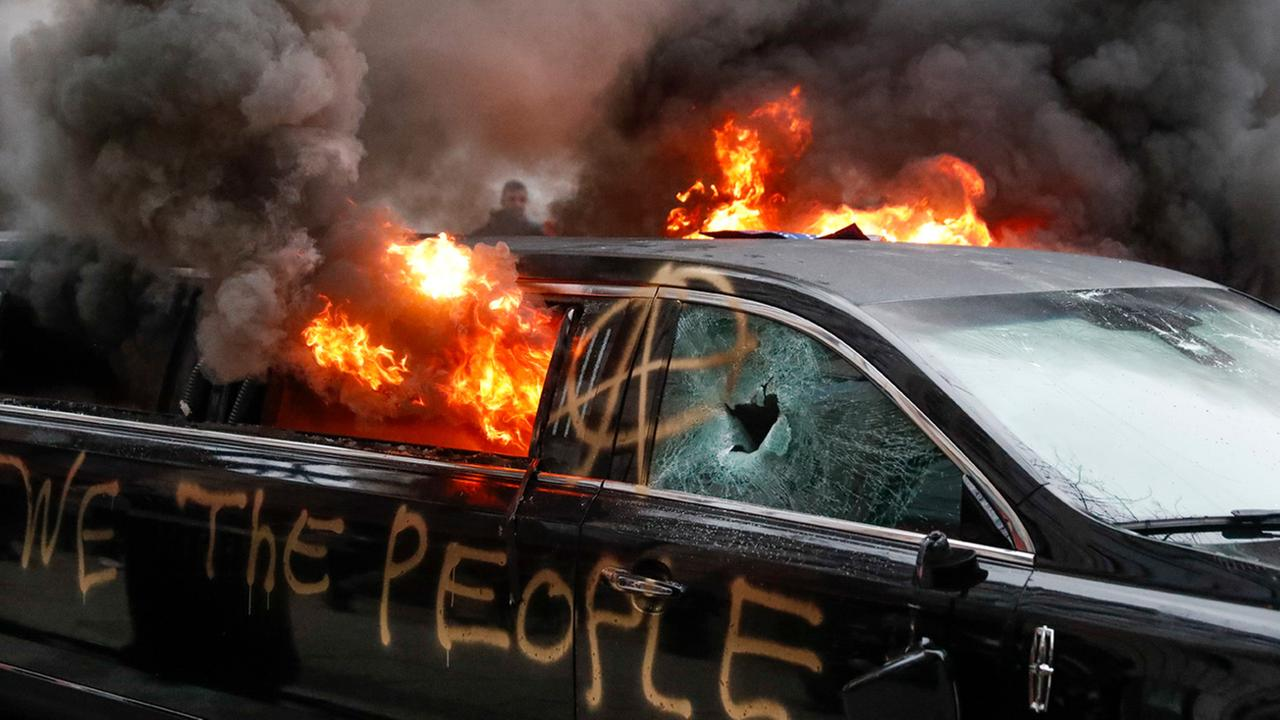 A parked limousine burns during a demonstration after the inauguration of President Donald Trump, Friday, Jan. 20, 2017, in Washington.