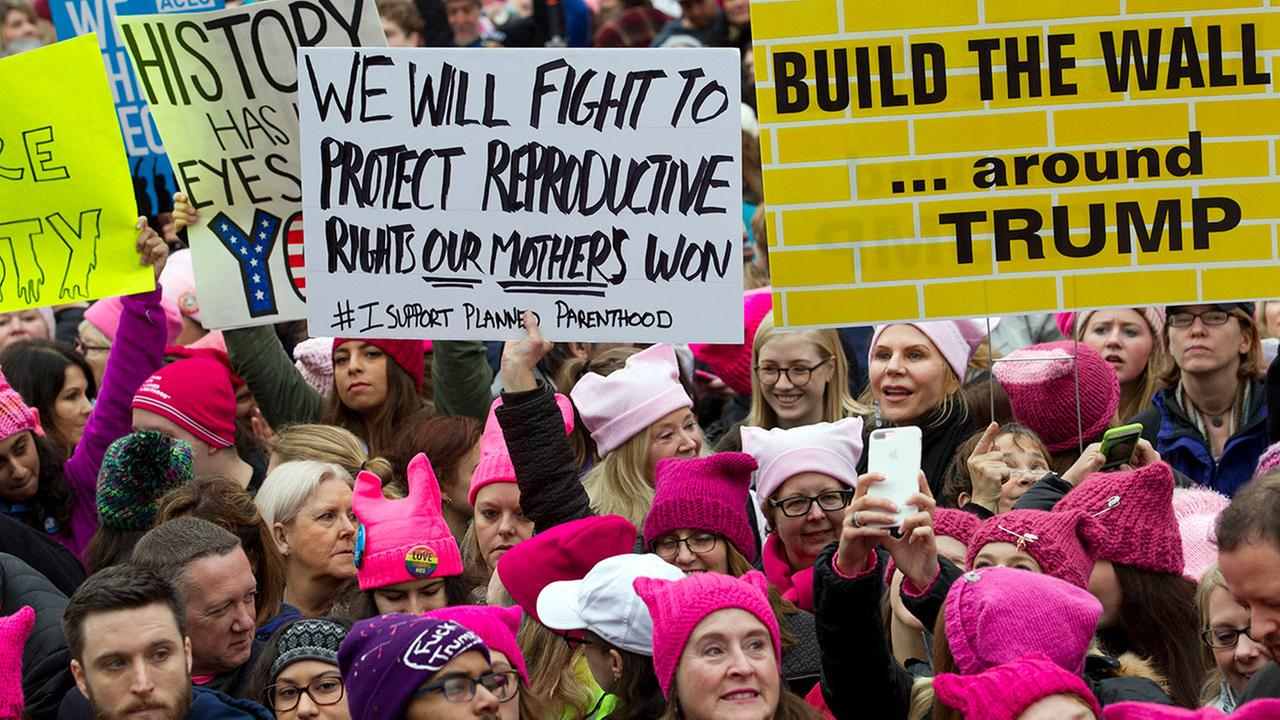Women with bright pink hats and signs begin to gather on the first full day of Donald Trumps presidency, Saturday, Jan. 21, 2017 in Washington.