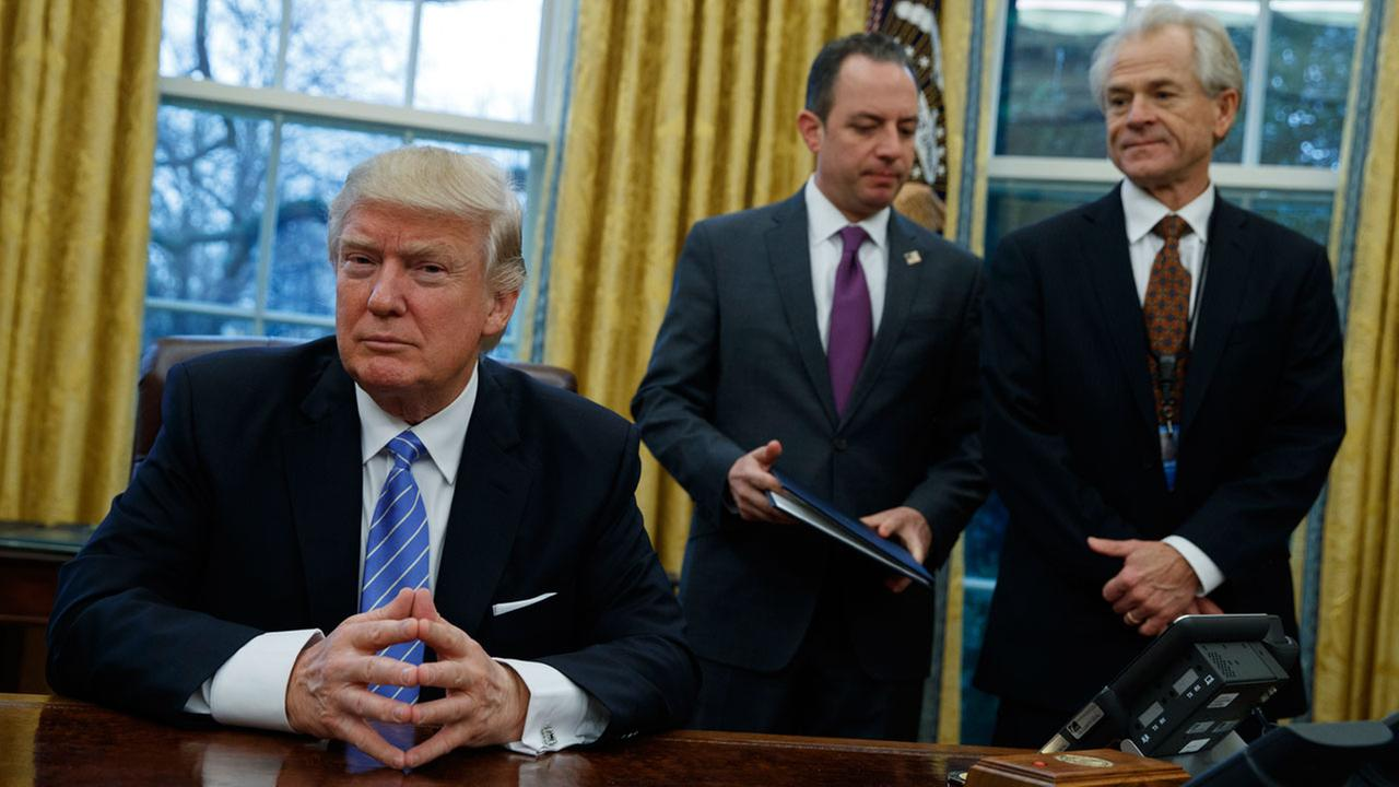 National Trade Council adviser Peter Navarro, right, and White House Chief of Staff Reince Priebus, center, await President Donald Trumps signing three executive orders.