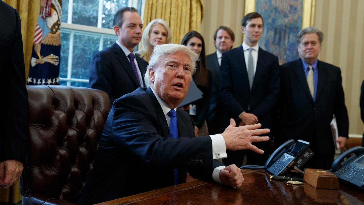 President Trump talks with reporters n the Oval Office of the White House in Washington, Tuesday, Jan. 24, 2017, before signing an executive order on the Keystone XL pipeline.
