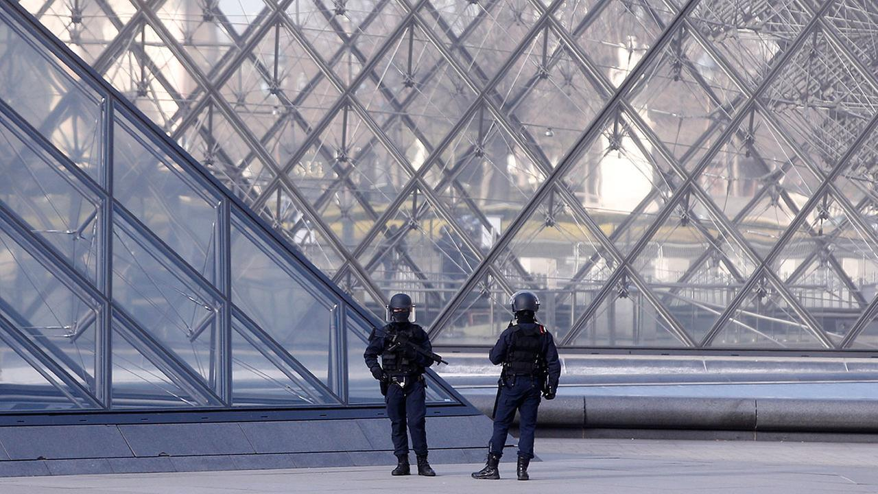 Police officers patrol at the pyramid outside the Louvre museum in Paris,Friday, Feb. 3, 2017.