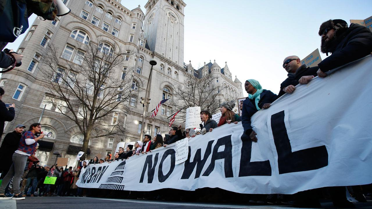 Protesters march along Pennsylvania Avenue past the Trump International Hotel during a rally protesting the immigration policies of President Donald Trump.