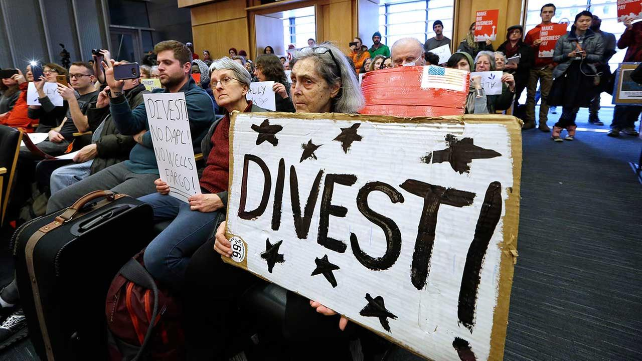 Cynthia Lynet holds a sign in favor of divestiture during a Seattle City Council meeting on Tuesday, Feb. 7, 2017.