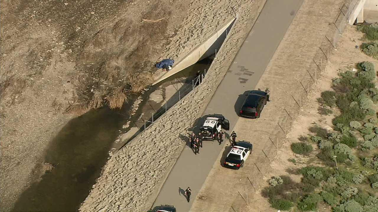Police officers are seen near a riverbed in Anaheim amid a search for a possibly armed suspect.