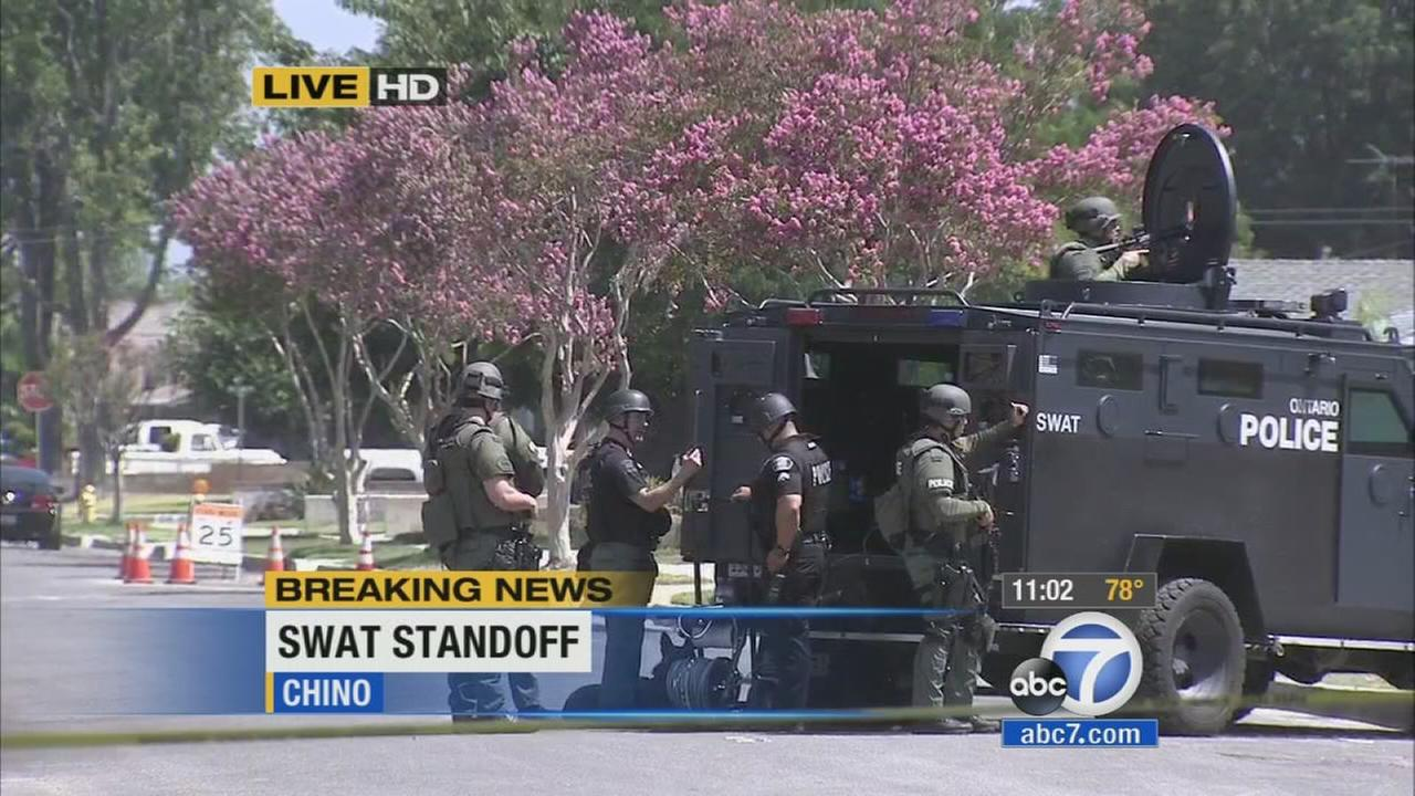 A SWAT team responds to a house in Chino, where two robbery suspects were barricaded on Thursday, July 10, 2014.