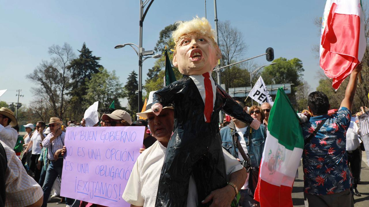 A woman holds a pinata depicting U.S. President Donald Trump during a march demanding respect for Mexico and its migrants, in Mexico City, Sunday, Feb 12, 2017.