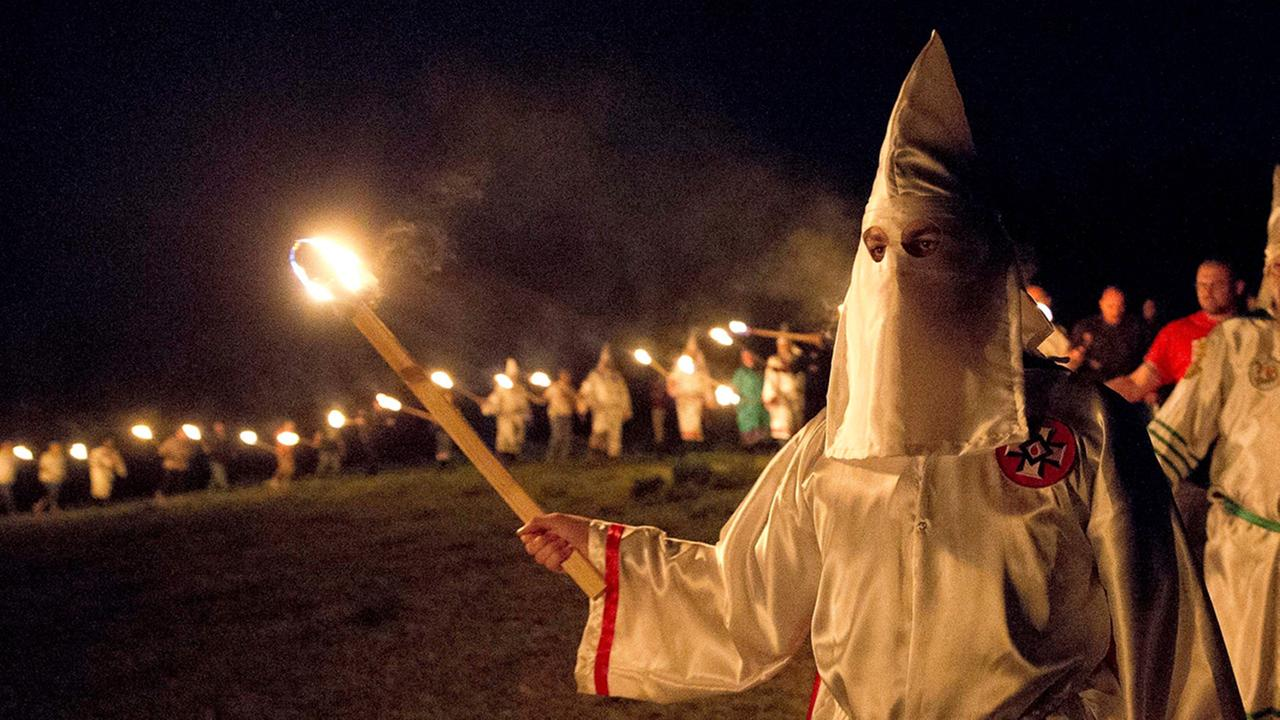 In this Saturday, April 23, 2016 photo, members of the Ku Klux Klan participate in cross burnings after a White Pride, rally, in rural Paulding County near Cedar Town, Ga.