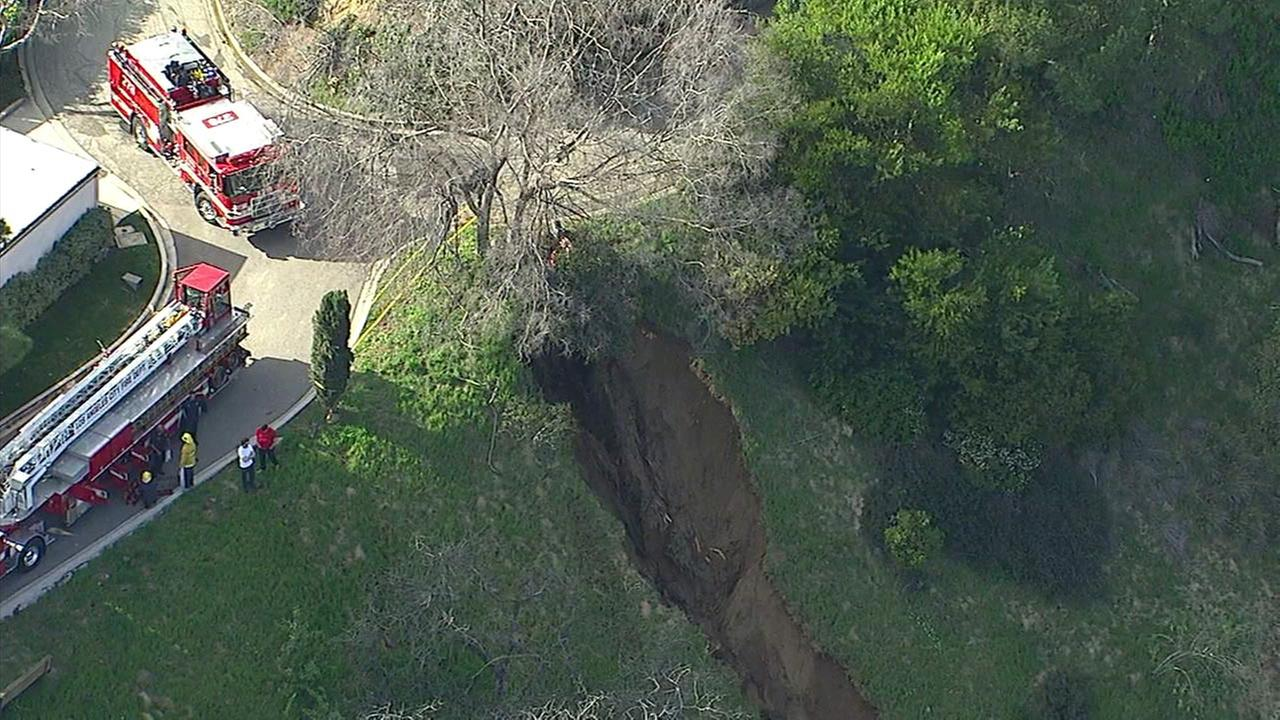 A large crack can been seen in a hillside in the area of West Burroughs Road in Beverly Crest, Los Angeles, on Monday, Feb. 13, 2017.