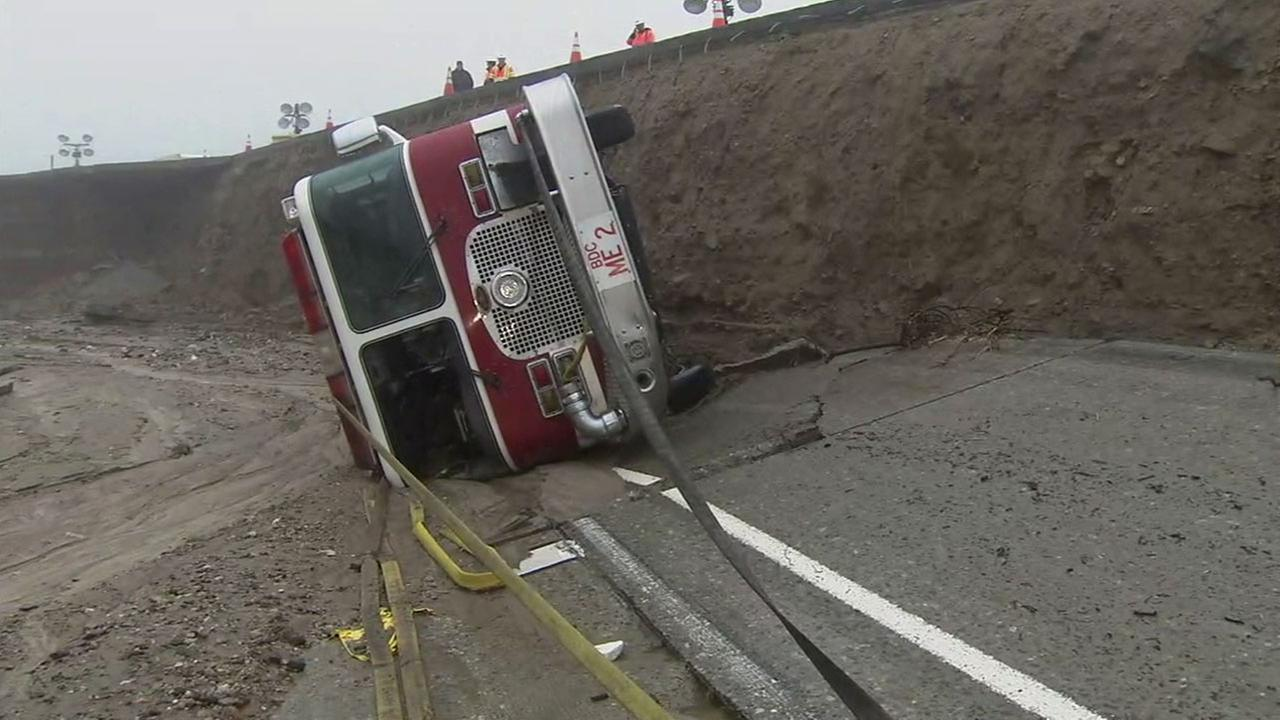 A San Bernardino County fire truck sits on its side on Saturday, Feb. 18, 2017, after tumbling into a creek in the Cajon Pass after rains damaged the 15 Freeway.KABC