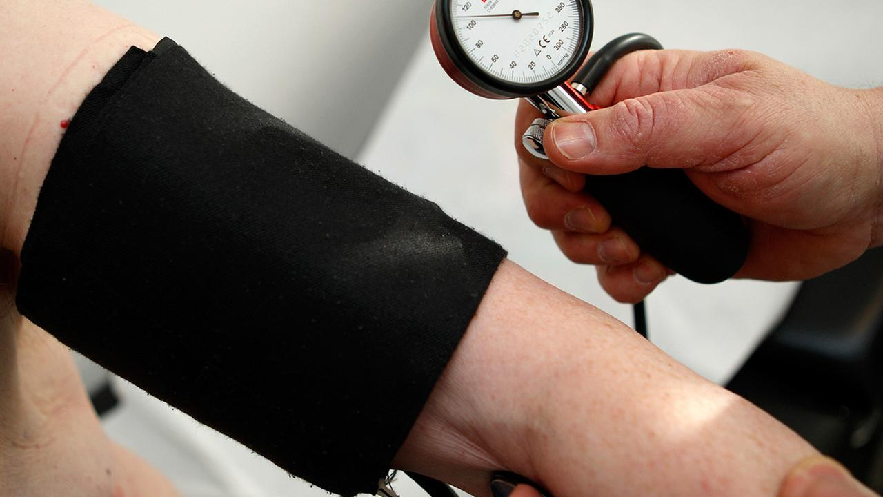 In this file photo, a general practitioner measures the blood pressure of a man.