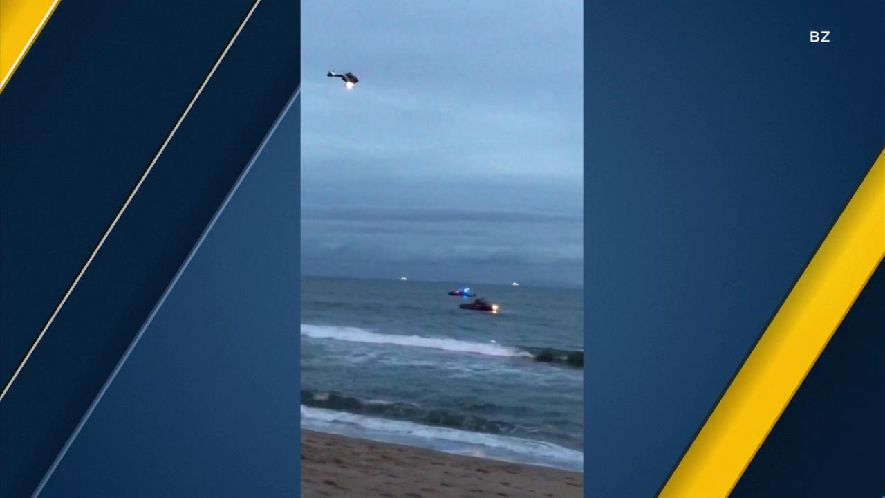A bystanders video shows a Coast Guard helicopter and boats searching for a missing swimmer off Bolsa Chica State Beach.