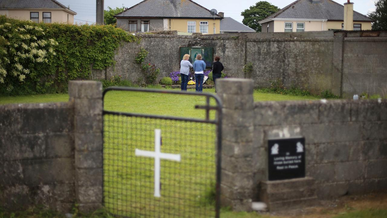 In this June 7, 2014 file photo members of the public at the site of a mass grave for children who died in the Tuam mother and baby home, in Tuam, County Galway.