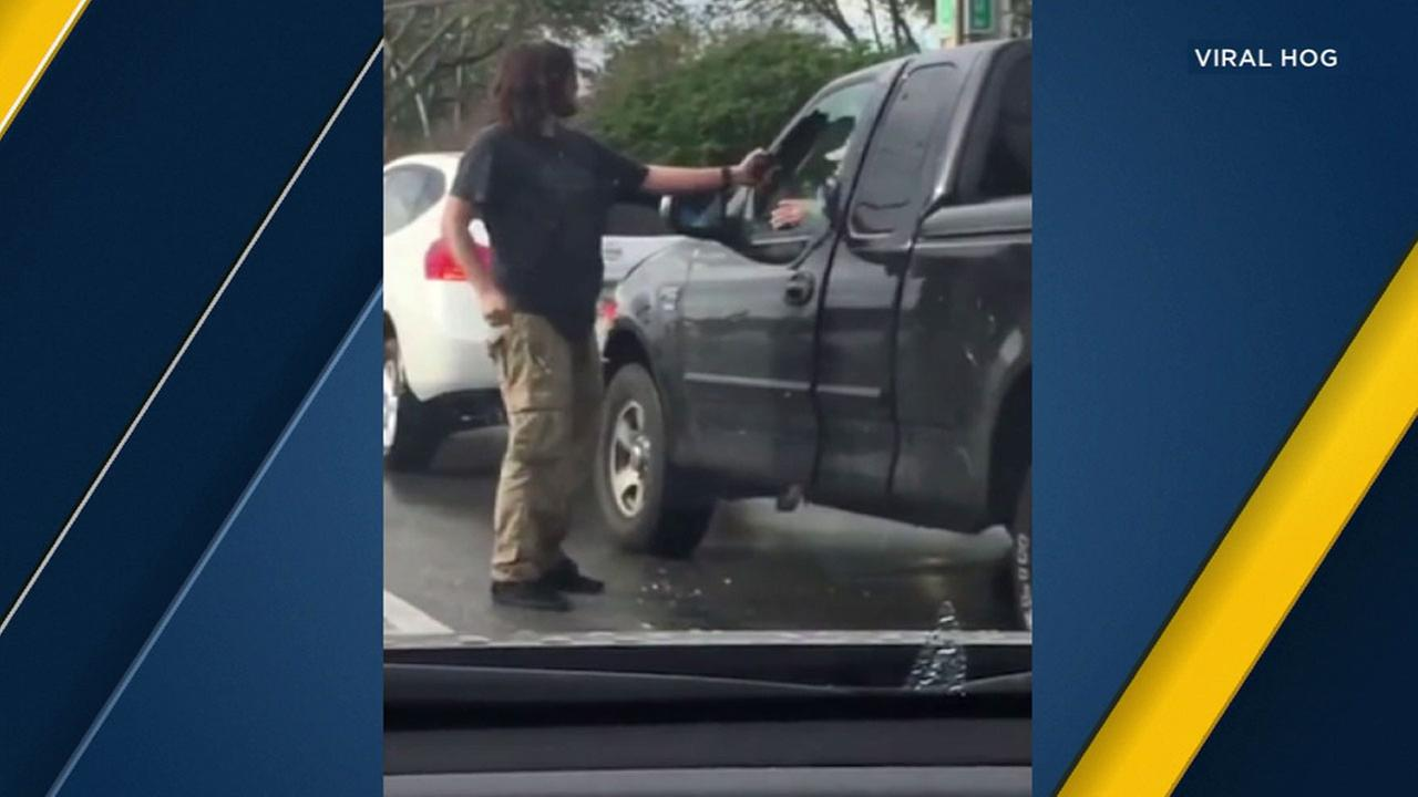 A BMW driver smashes the window of a pick-up truck and is seen pepper spraying the driver.