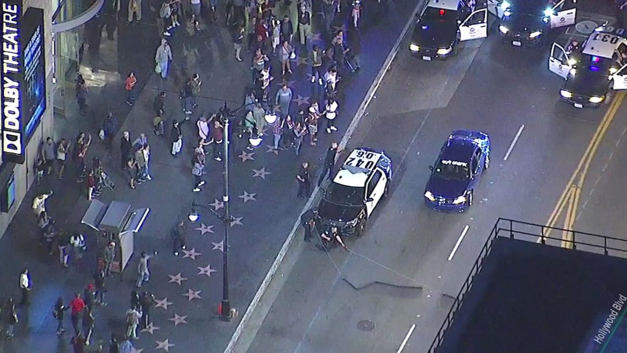 A grand theft auto suspect waves to a crowd of onlookers along Hollywood Boulevard during a bizarre chase in Hollywood on Thursday, March 9, 2017.
