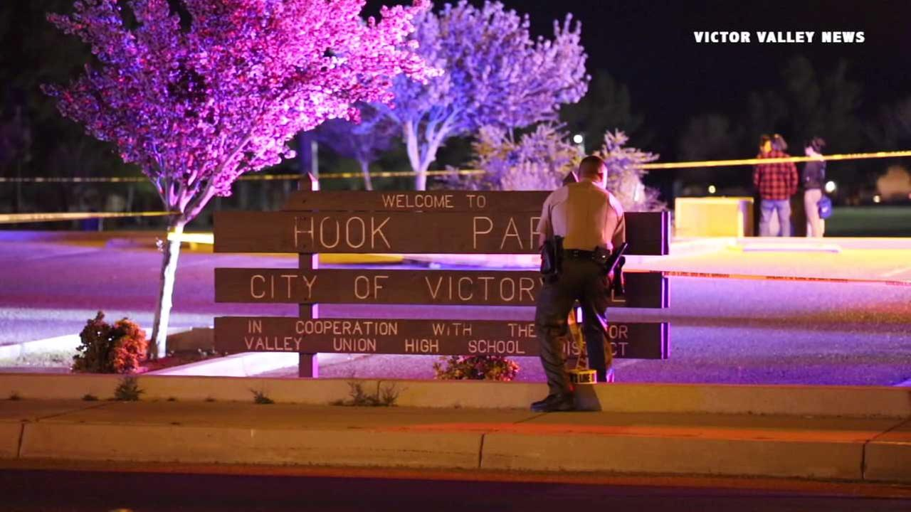 Sheriffs deputies are seen rolling out crime scene tape at Hook Park in Victorville on Wednesday, March 15, 2016.
