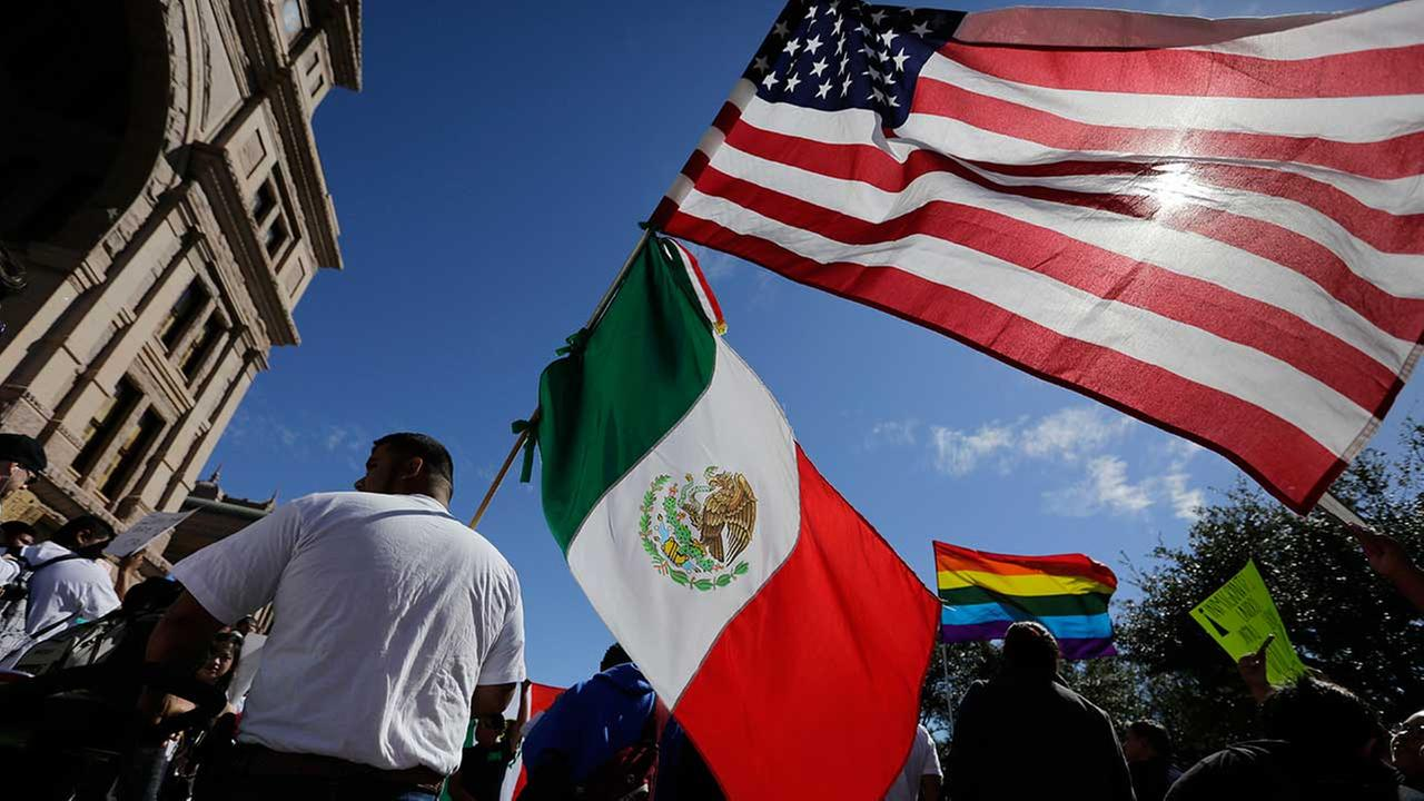 A man hold the U.S and Mexico flags during a march and rally during an immigration protest, Thursday, Feb. 16, 2017, in Austin, Texas.