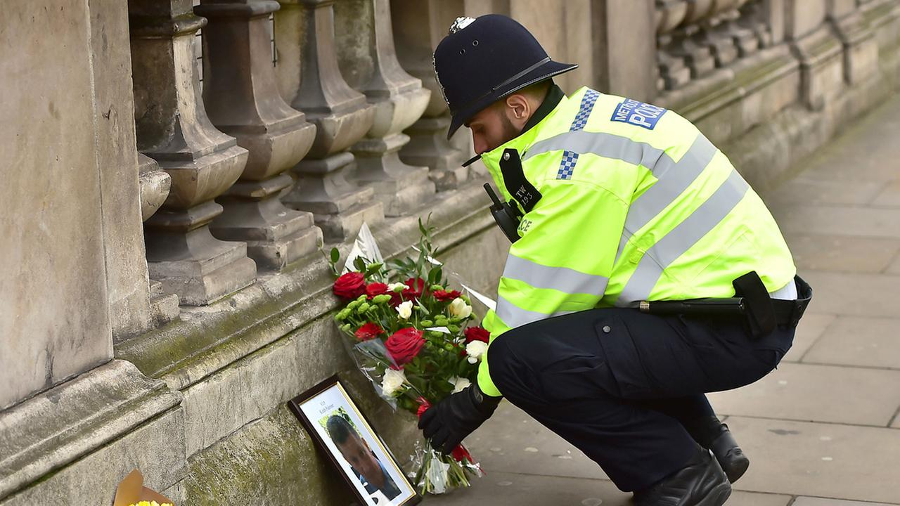 A police officer places flowers and a photo of fellow police officer Keith Palmer, who was killed in an attack in Whitehall near the Houses of Parliament in London.
