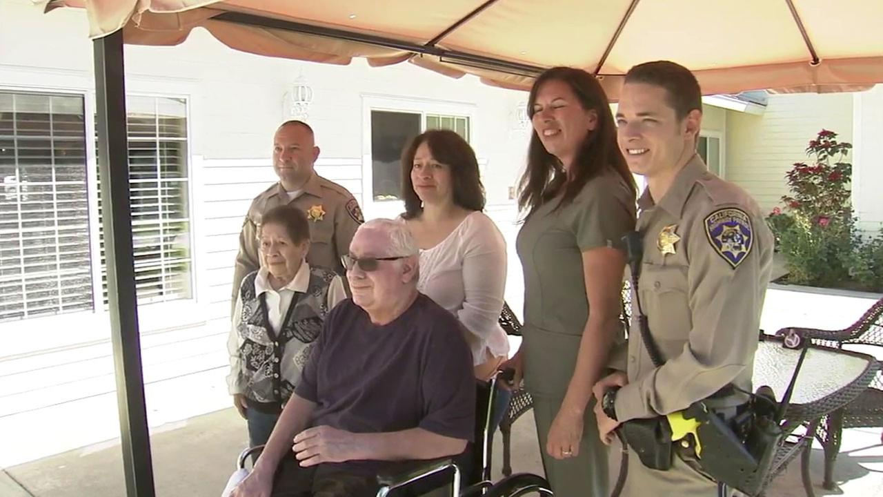 Victor Garcia Jr sits for a photo surrounded by family and two CHP officers who helped save him from a burning car near Adelanto in November.