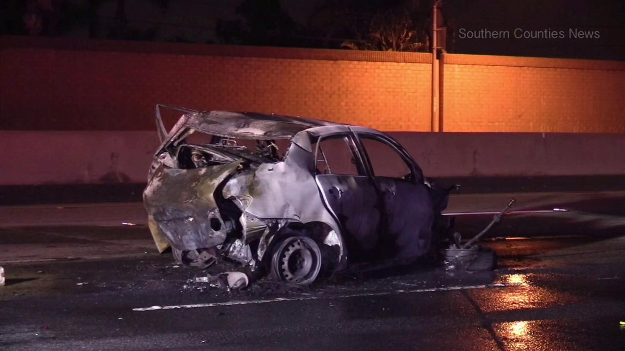 The wreckage of a burned-out car is seen on the 91 Freeway in Anaheim after a fatal crash on Saturday, March 25, 2017.
