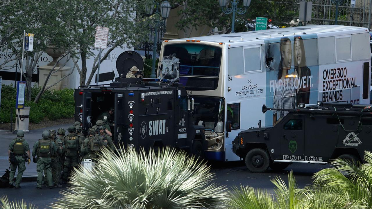 Las Vegas SWAT officers surround a bus along Las Vegas Boulevard, Saturday, March 25, 2017, in Las Vegas. Police say part of the Strip has been closed down after a shooting.