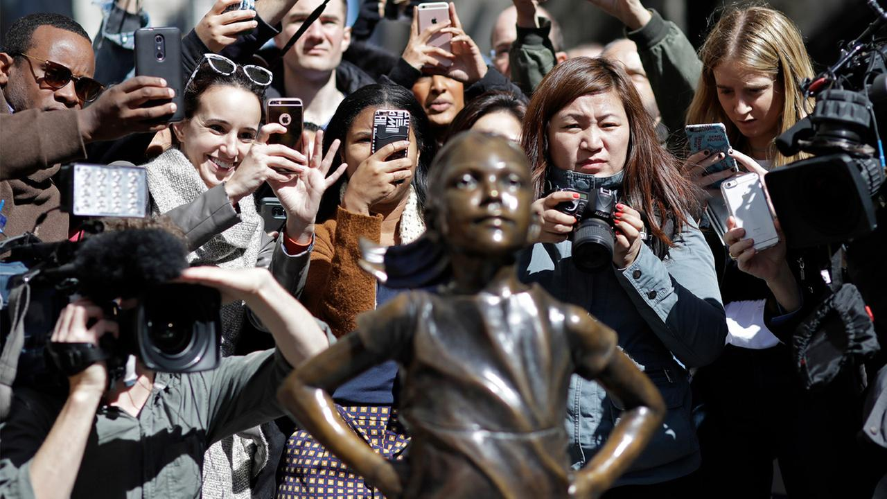 People stop to photograph the Fearless Girl statue, Wednesday, March 8, 2017, in New York.