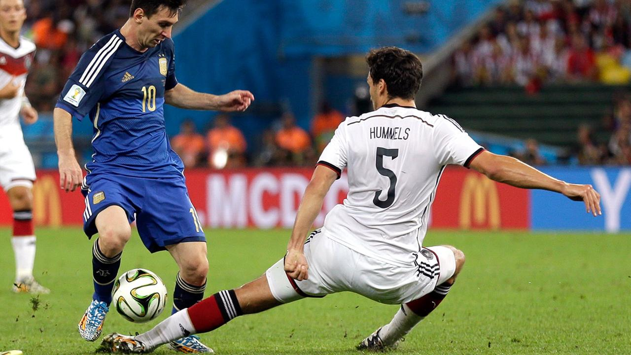 Germanys Mats Hummels tries to kick the ball away from Argentinas Lionel Messi during the World Cup final soccer match between Germany and Argentina at the Maracana Stadium. <span class=meta>(Natacha Pisarenko)</span>