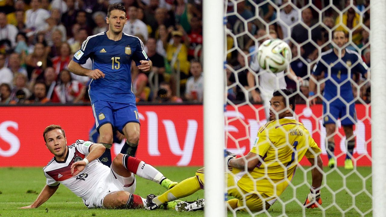 Germanys Mario Goetze kicks to score his sides first goal in extra time against Argentinas goalkeeper Sergio Romero during the World Cup final soccer match.