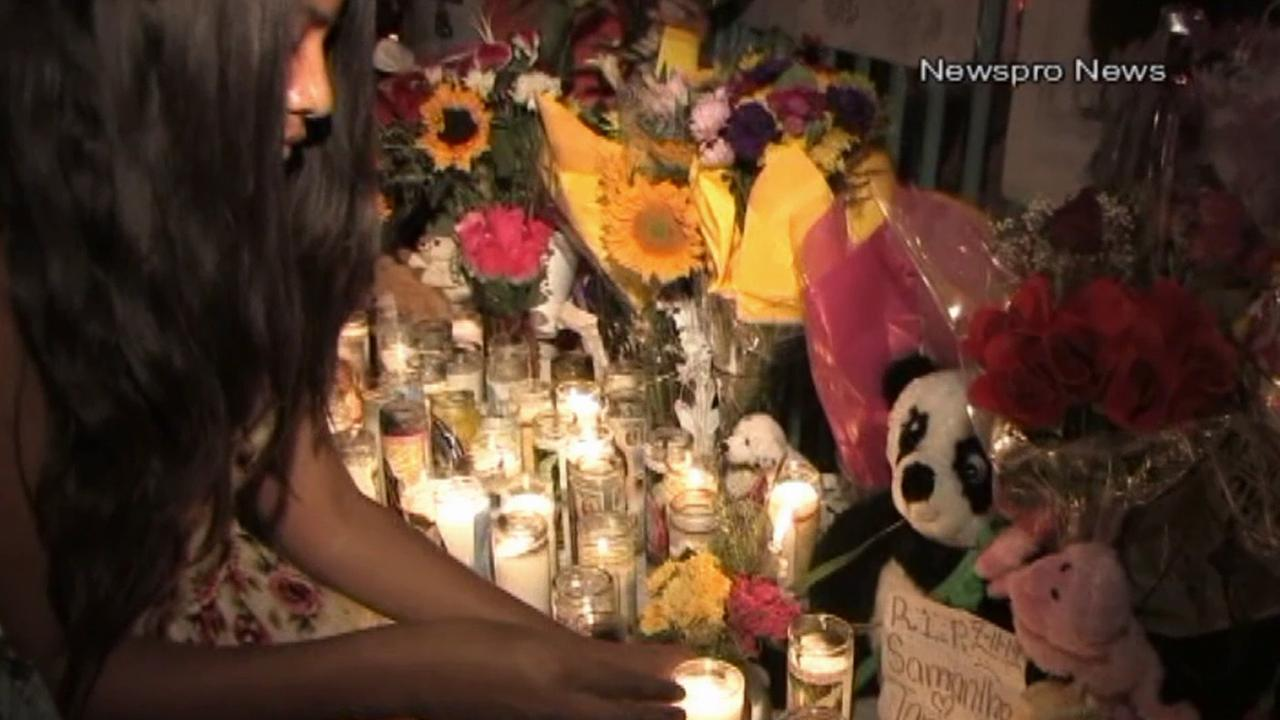 A woman places a candle at a vigil held for a 13-year-old girl killed in a hit-and-run crash in San Bernardino on Sunday, July 13, 2014.