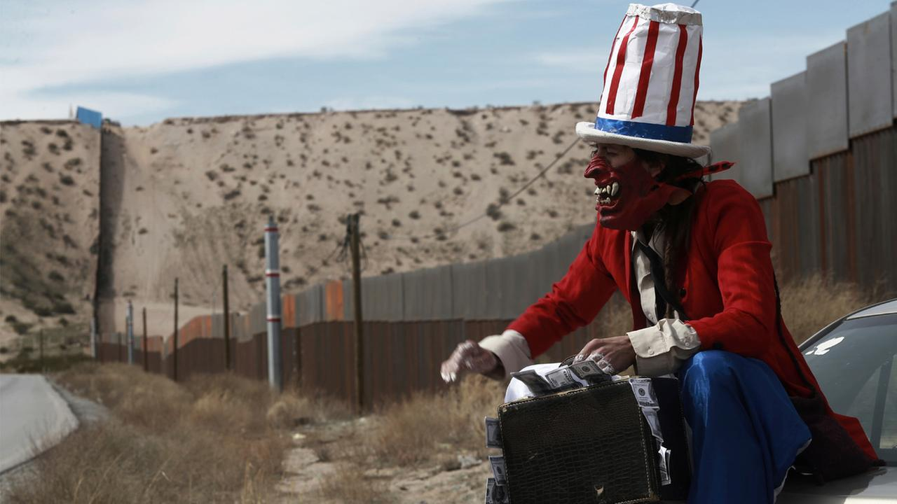 In this Sunday, Feb. 26, 2017 photo, a protester dressed as a diabolical version of Uncle Sam holds a suitcase full of money at the U.S. border fence in Ciudad Juarez, Mexico.
