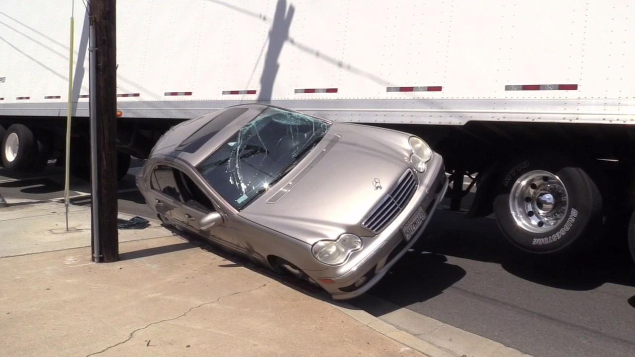 A Mercedes-Benz sedan stuck between a big rig and sidewalk after the driver attempted to pass up the semi-truck in Costa Mesa on Saturday, April 8, 2017.