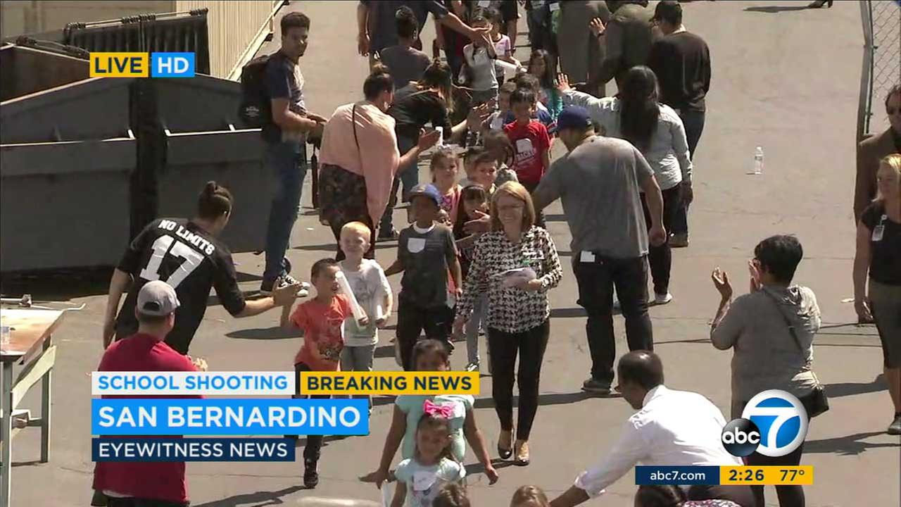 Students give high fives to school staff and volunteers after being released following a shooting at a San Bernardino elementary school on Monday, April 10, 2017.KABC